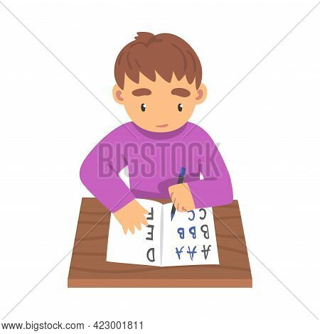 Cute Boy Sitting At His Desk And Writing, Elementary School Student Writing English Letters In Noteb