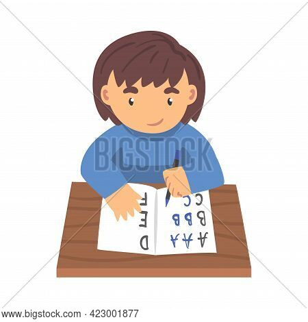 Cute Boy Sitting At Her Desk And Writing, Elementary School Student Writing English Letters In Noteb