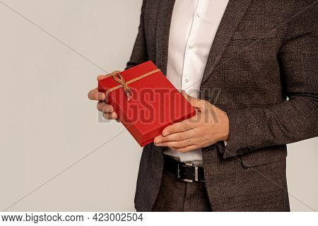 Partial View Of Man In Suit Holding Red Gift Box Isolated On Grey With Lilac Shade