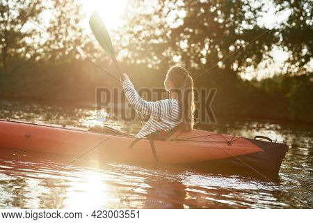 Caucasian Young Woman Looking Relaxed, Holding A Paddle, Kayaking In A Lake Surrounded By Nature On