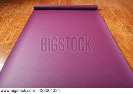 A Lilac-colored Yoga Mat Is Spread Out On The Wooden Floor With A Ganapati Figurine