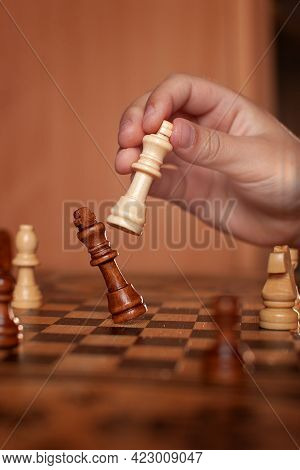Hand Holds White King Chess Piece And Hits Drops Black King Chess Piece Chessboard. Concept Victory