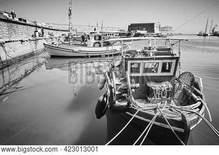 Fishing boats in Venetian Harbor of Heraklion, Crete Island, Greece. Black and white photography