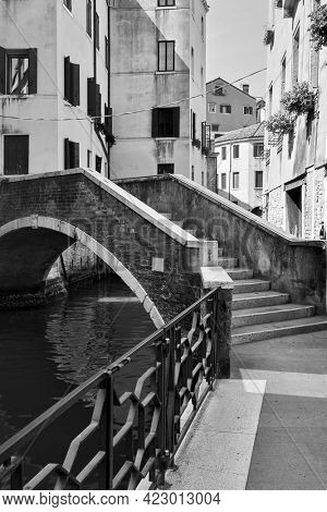Venice in Italy. Canal with small bridge. Black and white photography, venetian view
