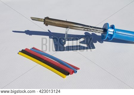 Electric Soldering Iron With Blue Handle And Heat Shrink Insulation On White Background