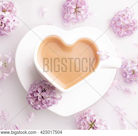 Cappuccino Coffee In A Cup And A Branch Of Lilac On A White Background . A Hot Drink. Relax. The Con