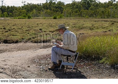 Mackay, Queensland, Australia - June 2021: Senior Male Retiree Learning To Fly A Drone On Saltpans P