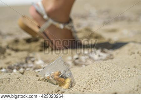 Plastic Cup Discarded On Sea Coast Ecosystem With Woman Walking On Background, Nature Waste Pollutio