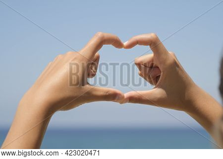 Woman Hands While Doing Herth Sign Over Natural Sea Horizon Background, Love