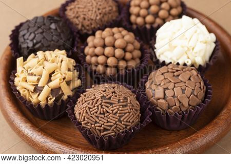 Typical Brazilian Brigadeiros, Various Flavors On A Wooden Plate.