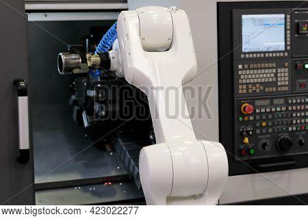 Robot Loading The Workpiece Into Cnc Lathe Machine. Selective Focus.