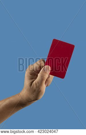Referee Hand Holding Red Punishment Card On Blue Background