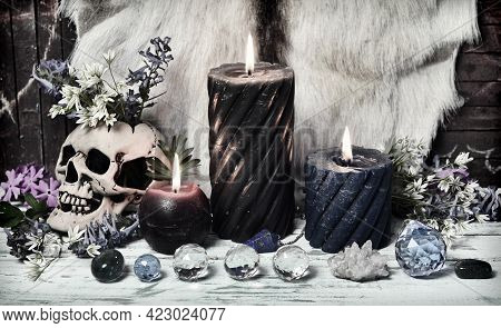 Grunge Still Life With Crystal Stones, Burning Candles And Skull With Flowers On Witch Altar Table.
