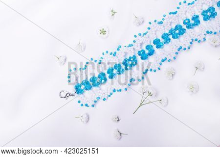 Fashionable Beaded Accessories. Handmade Jewelry: Bracelet Of White And Blue Beads On A White Backgr