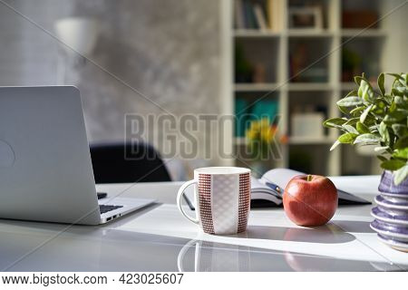 Laptop and cup of coffee or tea on desk at home. Cosy study room in morning lights.