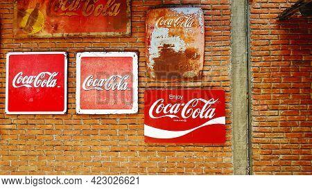 Bangkok, Thailand - September 5, 2020: Many Coca-cola Billboard Or Rusty Sign Hanging On Brown Brick