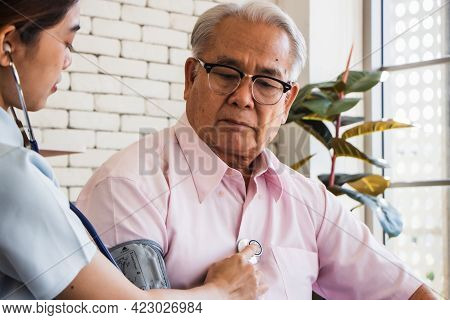 Senior Man At The Nursing Home Concept. Nurse Measures The Elderly's Blood Pressure And Pulse At The