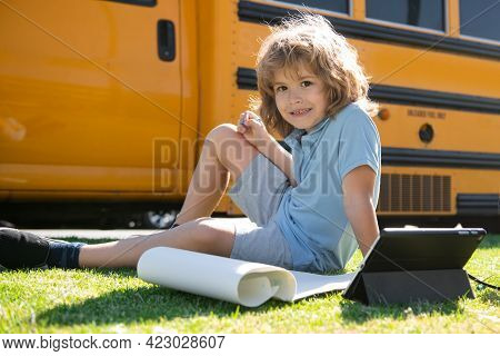 Happy Schoolboy Laying On Grass With Tablet Outdoor Near School Bus.