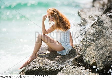 Side View Of Serene Woman Sitting On Sandy Rocky Beach Against Blue Waves. Attractive Young Woman We