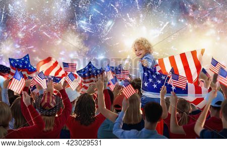 American Family Celebrating 4th Of July. People Watching Independence Day Fireworks Holding Us Flag.