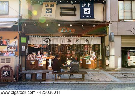 Japan- February 22, 2019: Two Women Or Friends In Coat Sitting And Talking Bench In Front Of The Sna