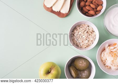 Probiotics Food On Light Green Background. Sauerkraut, Pickled Cucumbers, Natural Yogurt, Cheese, Al