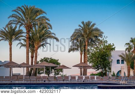 Relaxing By The Pool In A Luxurious Beachfront Hotel Resort At Sunset Enjoying Perfect Beach Holiday