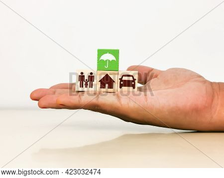 Insurance Coverage Concept. Hand Holding Wooden Blocks With Umbrella, Family, Car And House Icons.