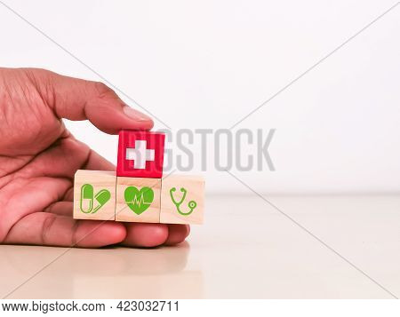 Hand Holding Wooden Cubes With Health Care Icons. Health Insurance Concept.