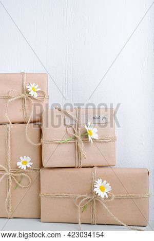 Set Of Gifts Box Wrapped With Brown Craft Paper And Decorated With Natural Chamomile Flowers. Top Vi
