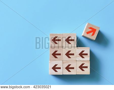 Individual And Standing Out From The Crowd Concept. Wooden Cubes With Red Arrow Facing The Opposite
