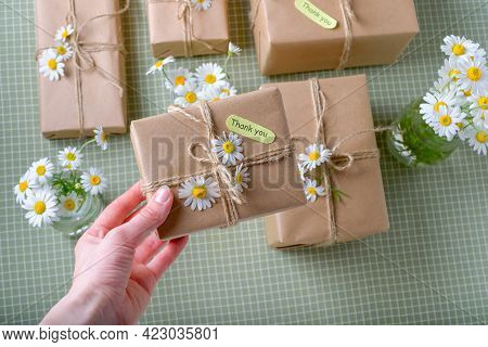 Female Hand Holding A Gift Or Present Box Wrapped In Kraft Paper Decorated With Flowers And Thank Yo