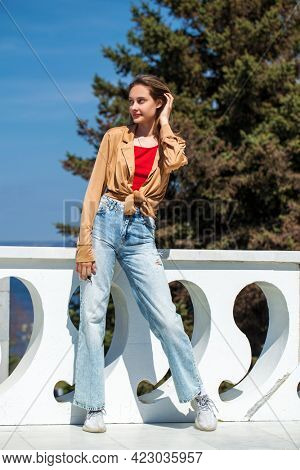 Full length portrait of a young stylish girl in a beige blouse with long sleeves and blue jeans