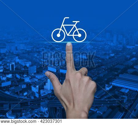 Hand Pressing Bicycle Flat Icon Over Modern City Tower, Street, Expressway And Skyscraper, Business