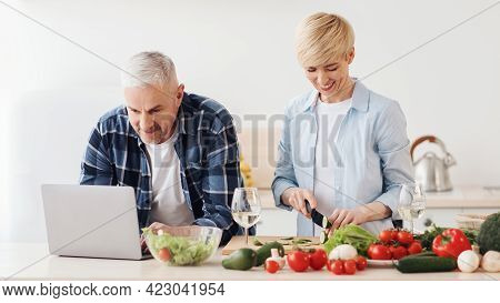 Happy Middle Aged 50s Couple Using Laptop, Preparing Healthy Food