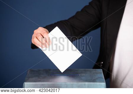 Voter putting vote in the ballot box. Election concept.