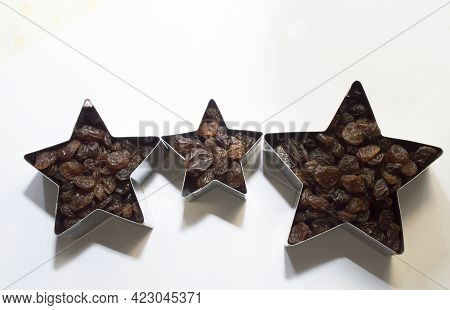 On A White Background Forms Of Stars Filled With Sweet Raisin Fruits Stars Of Large, Medium And Smal