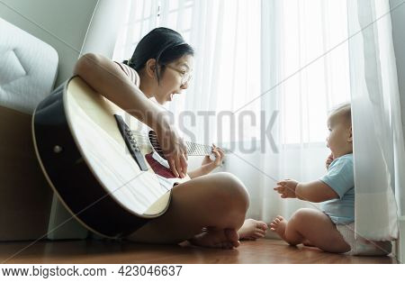 Happy Smiling Asian Mother And Little Cute Son Sitting On Wood Floor Singing And Playing Acoustic Gu