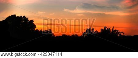 Dark Contrasting Banner With Silhouette Of Forest And Sunset Orange Sky With The Domes And Crosses O