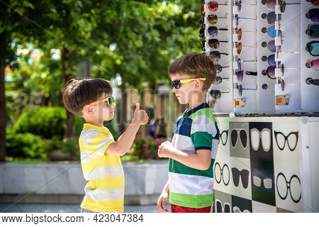 A Child And A Choice Of Sunglasses. Two Little Boys Are Standing In Sun-proof Glasses Against The Ba