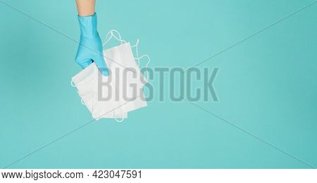 Hands Holding Face Masks Wear Blue Medical Latex Gloves On Mint Green Or Tiffany Blue Background.