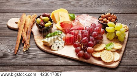 Cheese, meat, grapes and olives antipasto. Appetizer selection on wooden board