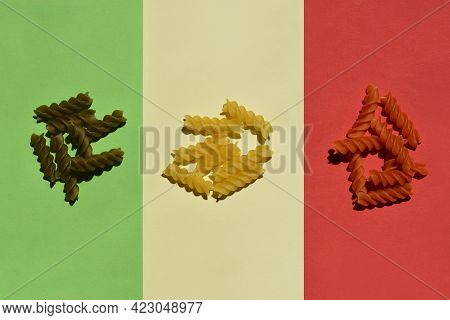 Close Up Of Dry Uncooked Fusilli Tricolore On Green, Pale Yellow And Red Paper