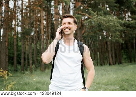 Happy Man Talking On A Cell Phone While Walking In The Woods. Athletic Traveler With Backpack Smilin