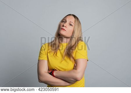 Displeased Mature Woman Wearing In Casual Yellow T Shirt, Standing With Crossed Arms And Looking Con
