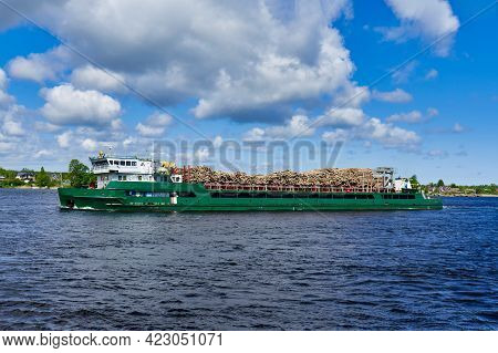 A Cargo Ship Transports Sawn Trees Down The River. Forestry And Wood Products Are An Important Part