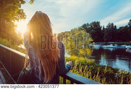 Woman enjoying the sunset over the Danube River in Regensburg