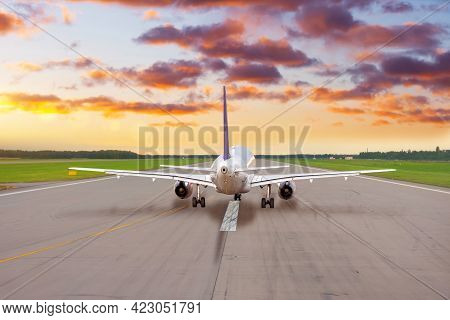 Passenger Plane On The Runway Ready To Take Off In The Evening At Sunset Sky.