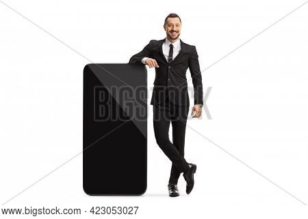 Full length portrait of a businessman standing next to a big mobile phone isolated on white background