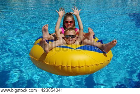 Boy and girl on inflatable float in outdoor swimming pool. Summer water play kids. Little children floating on yellow raft in aquapark.